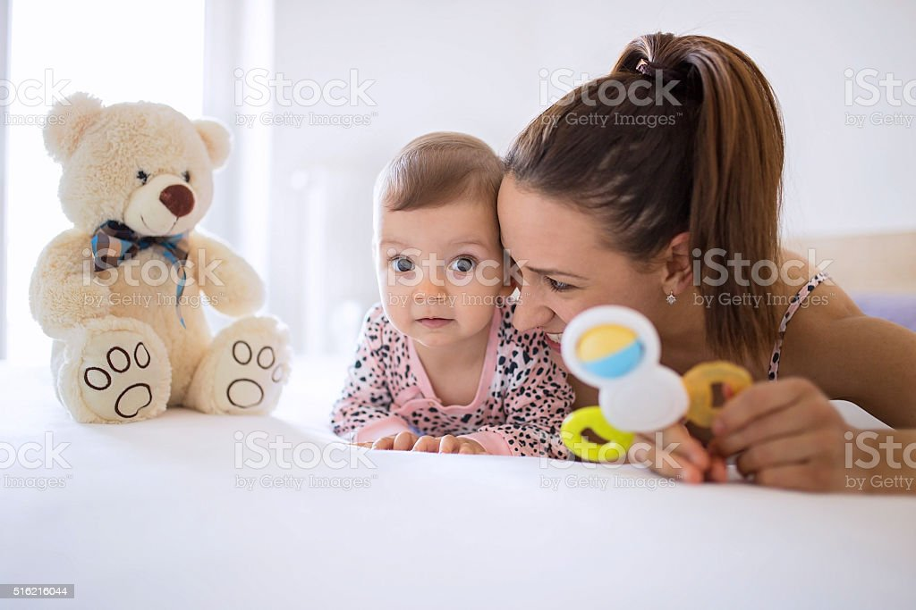 Teddy bear and rattle fun on the bed stock photo