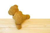 Teddy bear climbing the wood wall