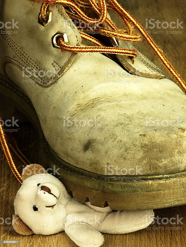Teddy bear crushed by a heavy, old military boot. stock photo