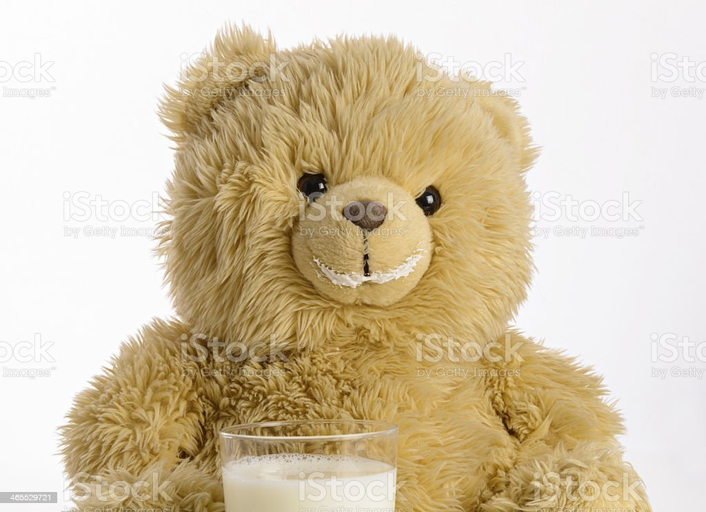Teddy bear drinks milk stock photo