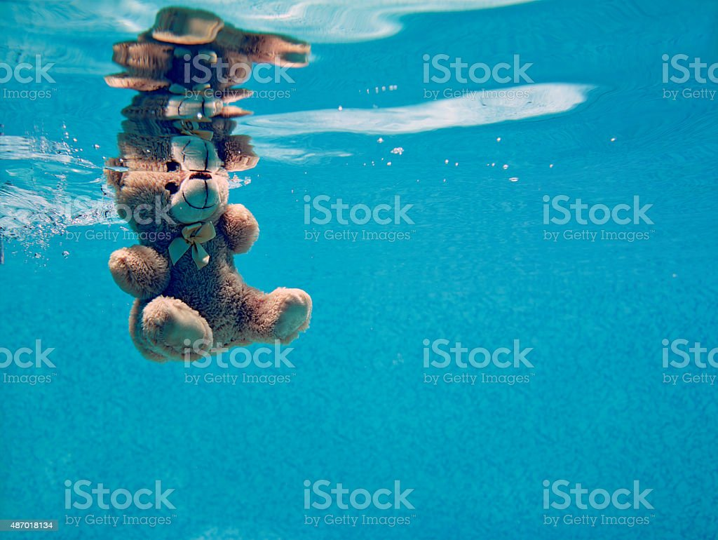 teddy bear drowning underwater stock photo