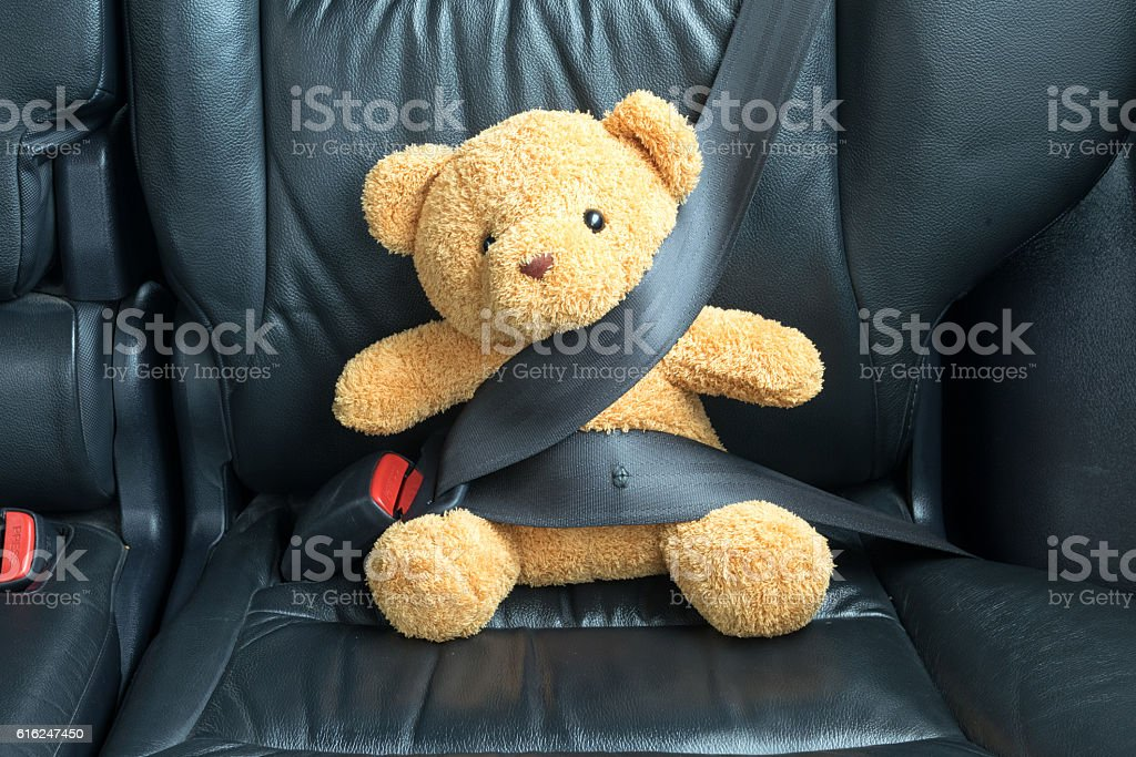 Teddy bear fastened in the back seat of a car