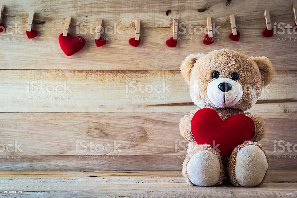 Teddy bear holding a heart-shaped pillow stock photo