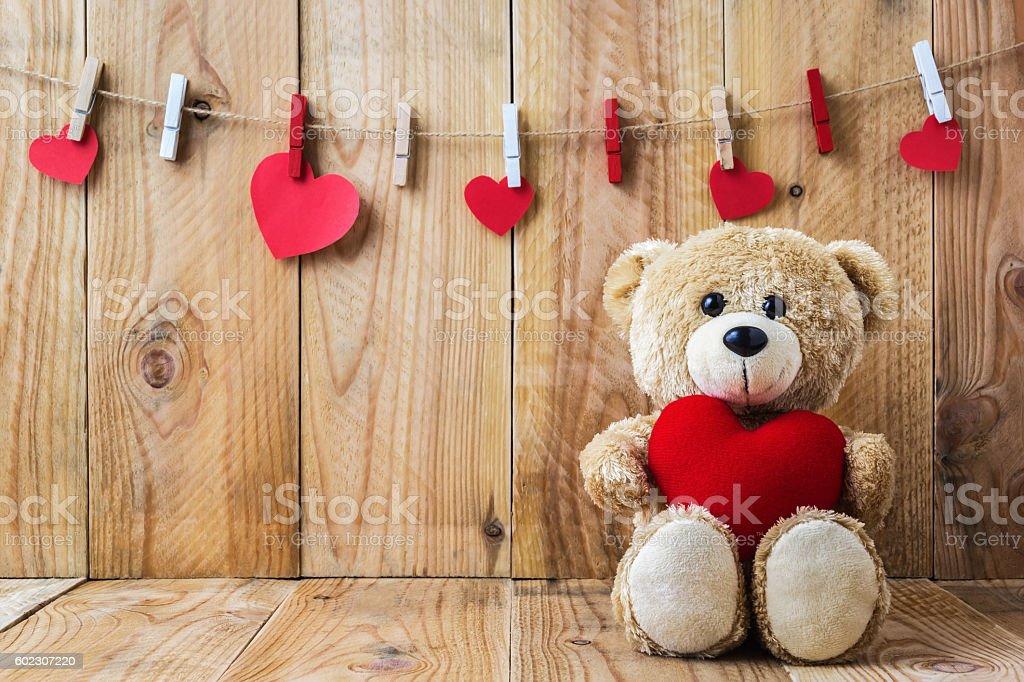 Teddy bear holding a heart-shaped pillow stock photo