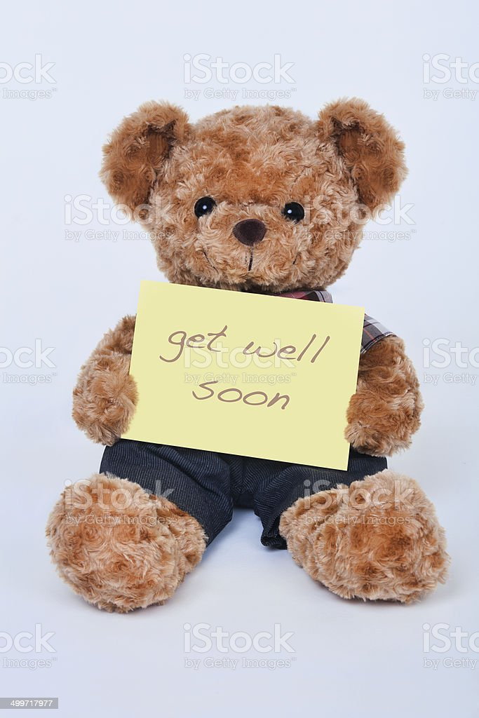 Teddy bear holding a  yellow sign saying Get Well Soon stock photo
