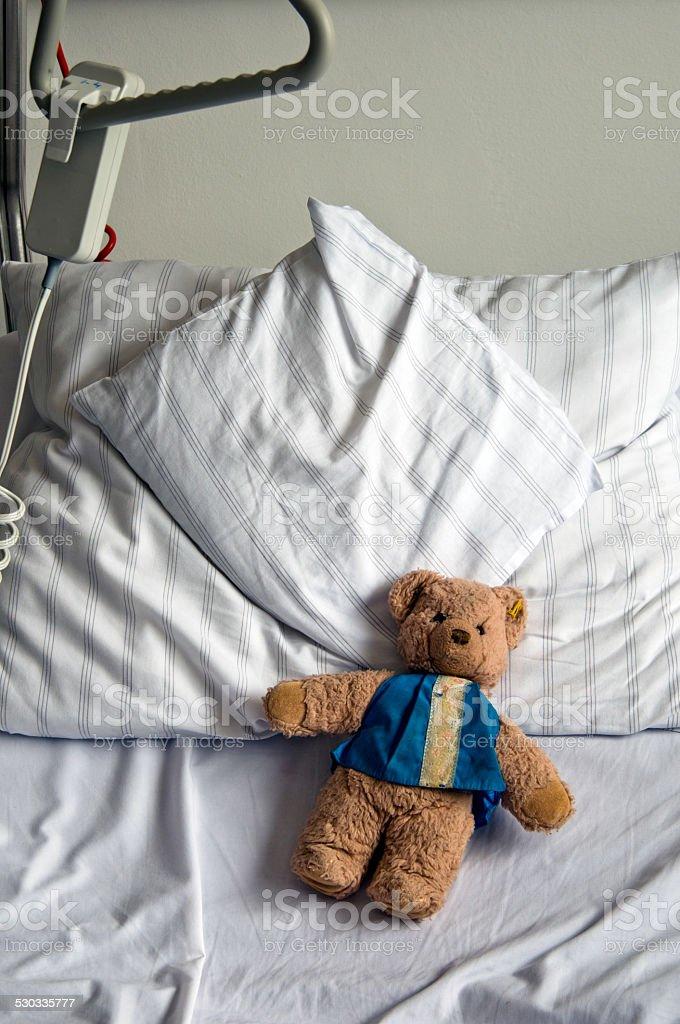 Teddy bear in a hospital bed stock photo