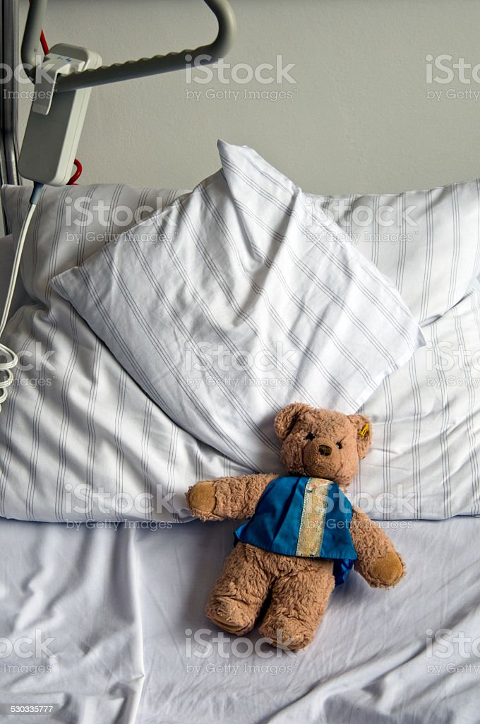 Teddy bear in a hospital bed stock photo