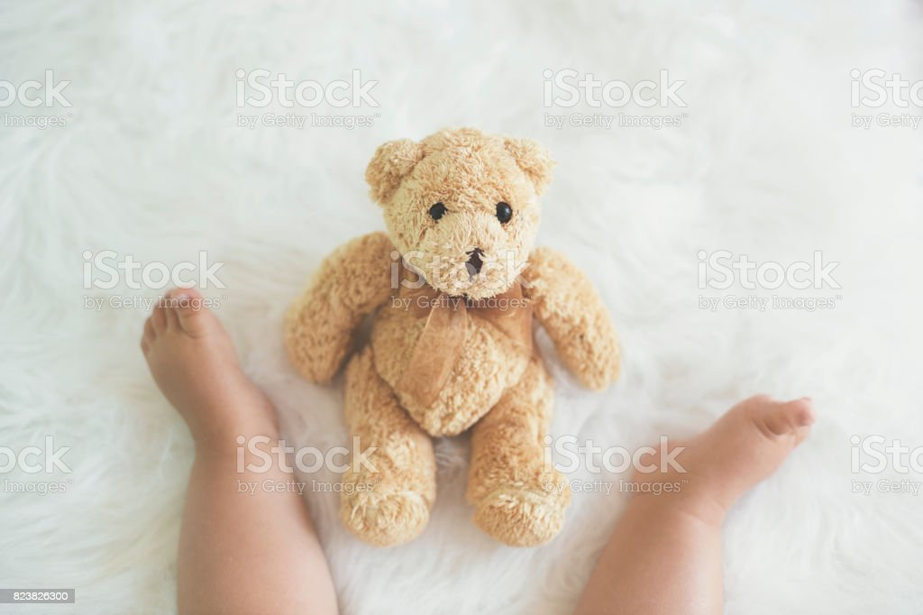 Teddy bear in front of baby, sitting on fluffy blanket - low section