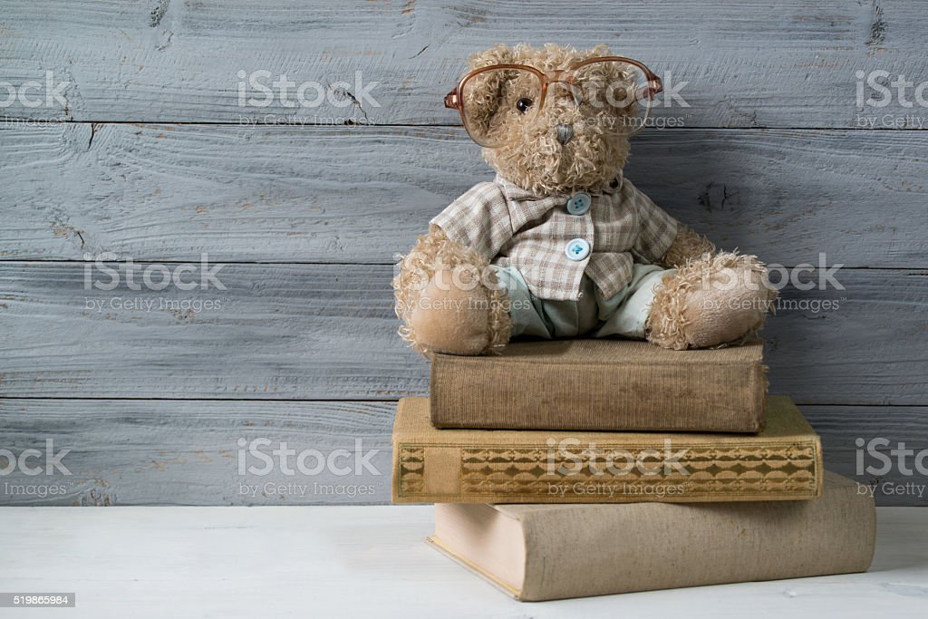 Teddy bear in reading glasses, the stack of old books stock photo