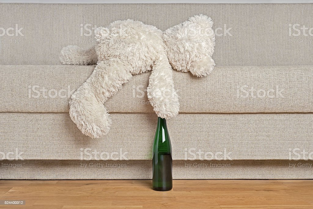 Teddy bear is laying on the sofa stock photo
