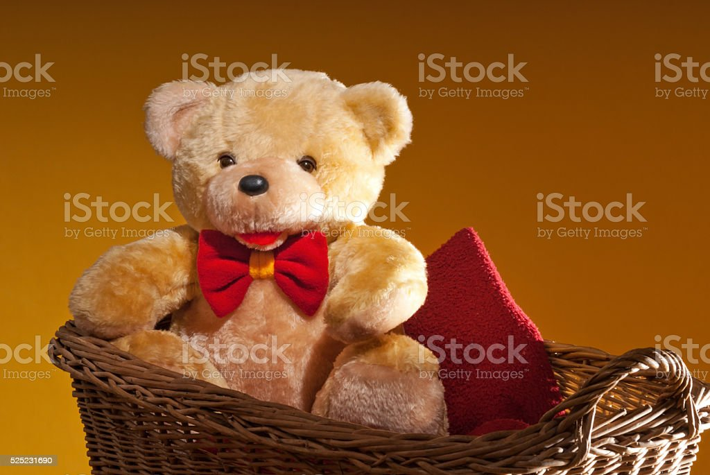 teddy bear is sitting in the wicker basket stock photo
