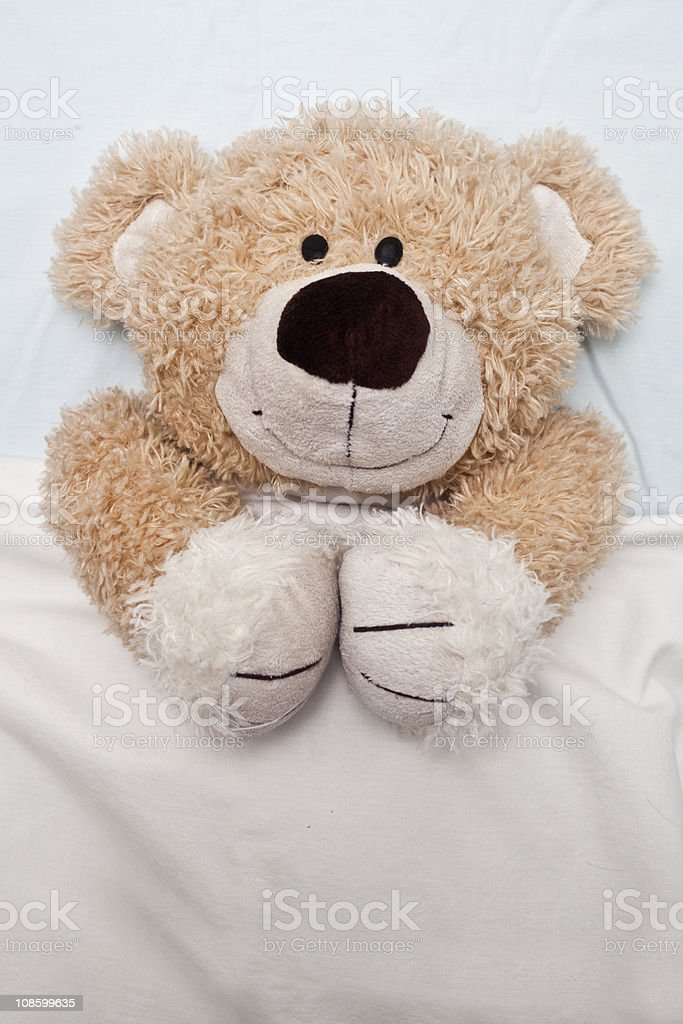 Teddy Bear Laying in Bed royalty-free stock photo