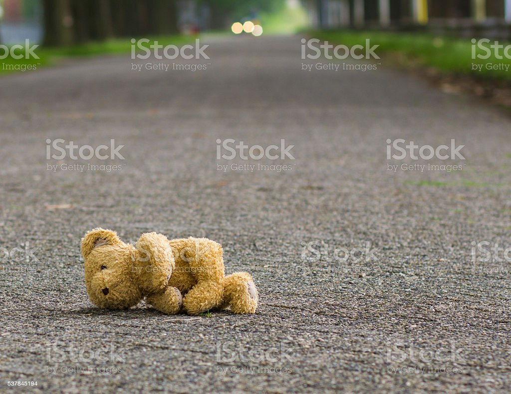 Teddy bear lies on the road stock photo