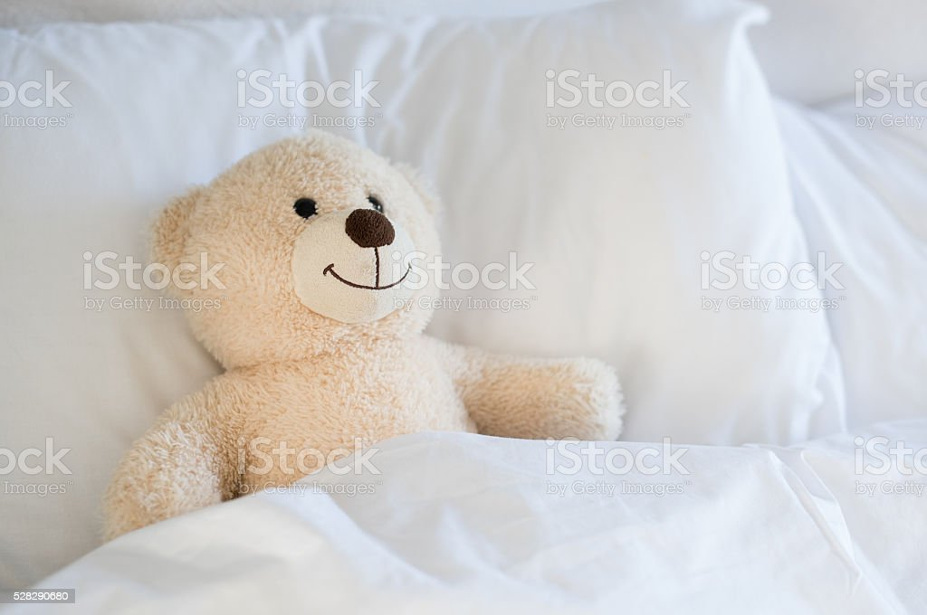 Teddy bear on bed stock photo