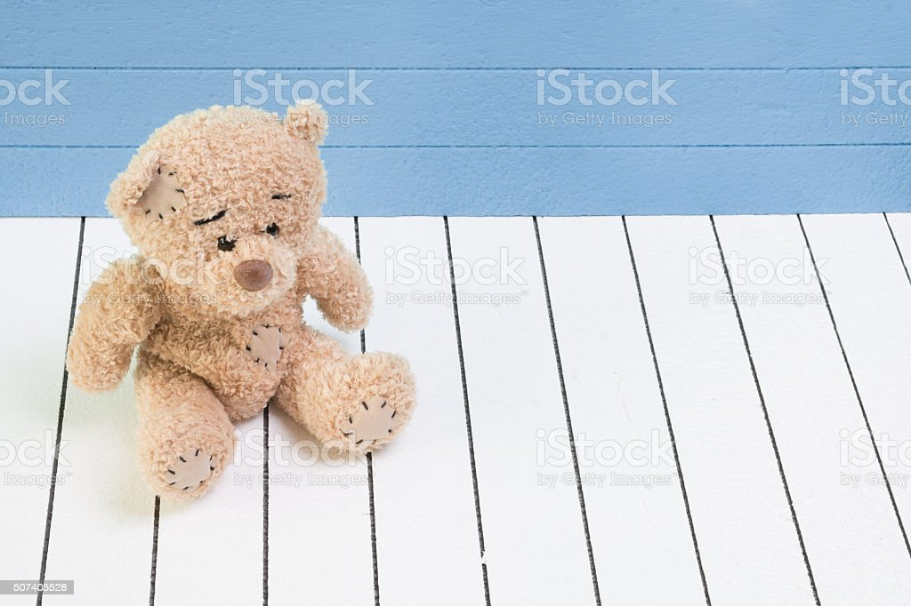 Teddy bear sitting on white wooden floor with blue-green stock photo