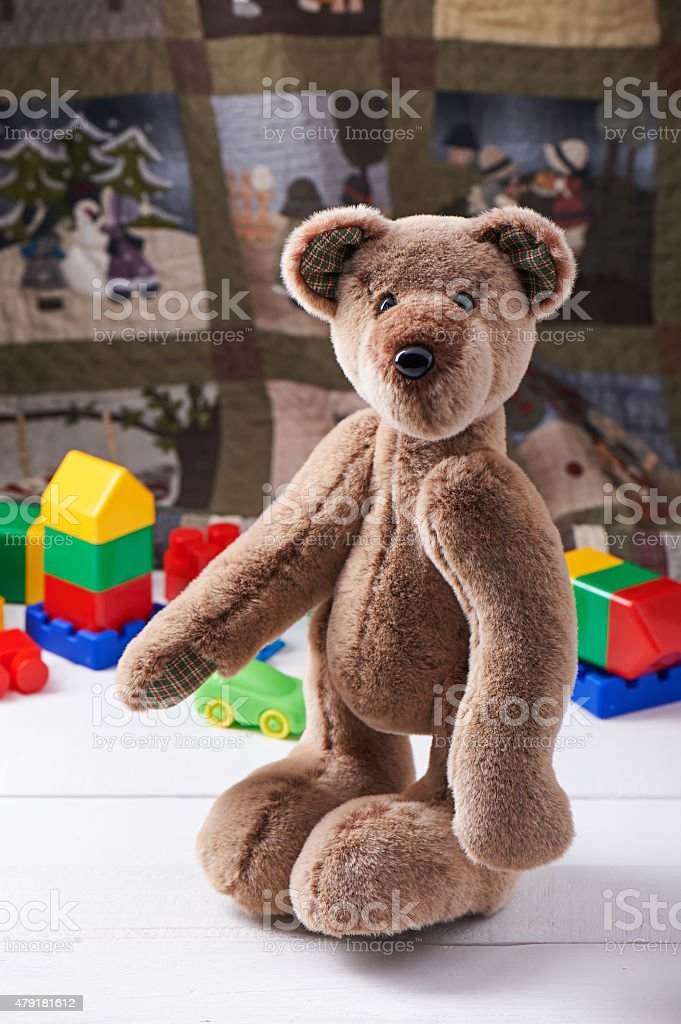 Teddy bear surrounded by blocks of children's plastic building kit stock photo