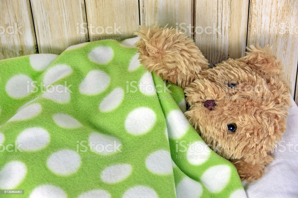 teddy bear under polka dot blanket stock photo