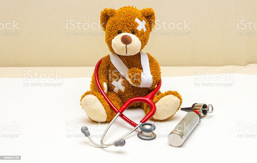 Teddy bear with bandages in pediatrician's office stock photo