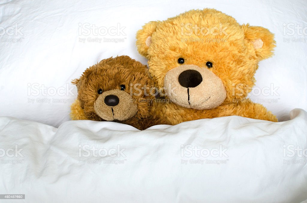 Teddy bears laying in bed stock photo