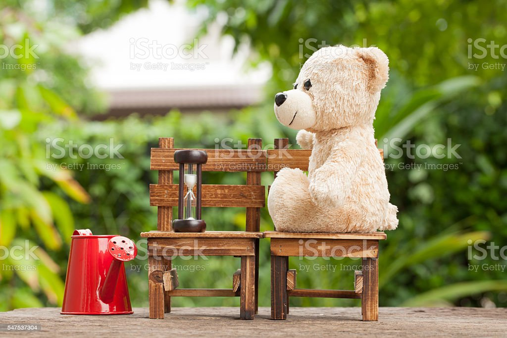 Teddy bears sitting on a wooden chair backyard. stock photo