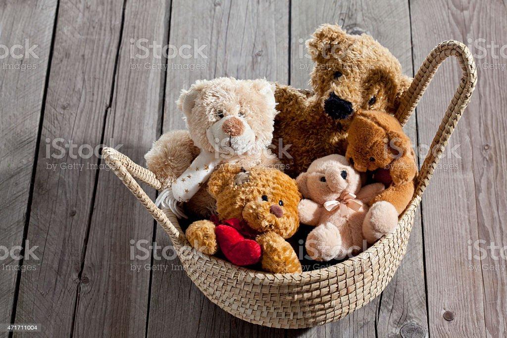 Teddy-bears in basket on wood stock photo