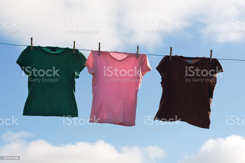 Tee Shirts Hanging on Clothesline Outdoors with Sky Background royalty-free stock photo