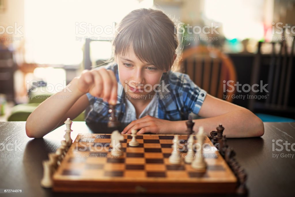 Teeange girl playing game of chess stock photo