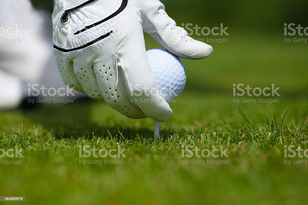 Teeing up a Golf ball stock photo