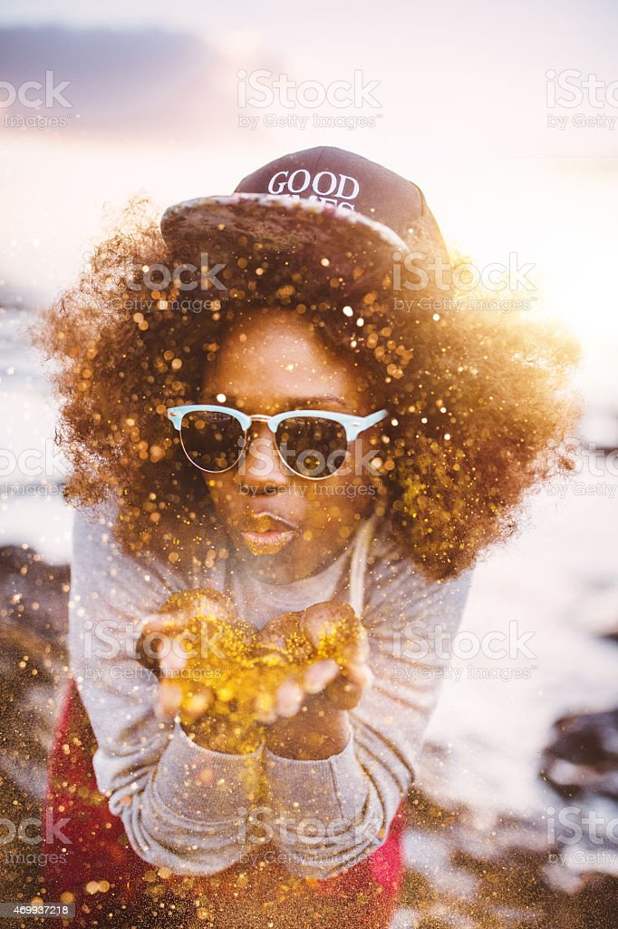 Teen Afro hipster blowing gold glitter from her hands stock photo