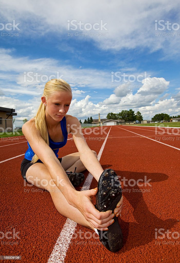 Teen athlete stretching before a race royalty-free stock photo