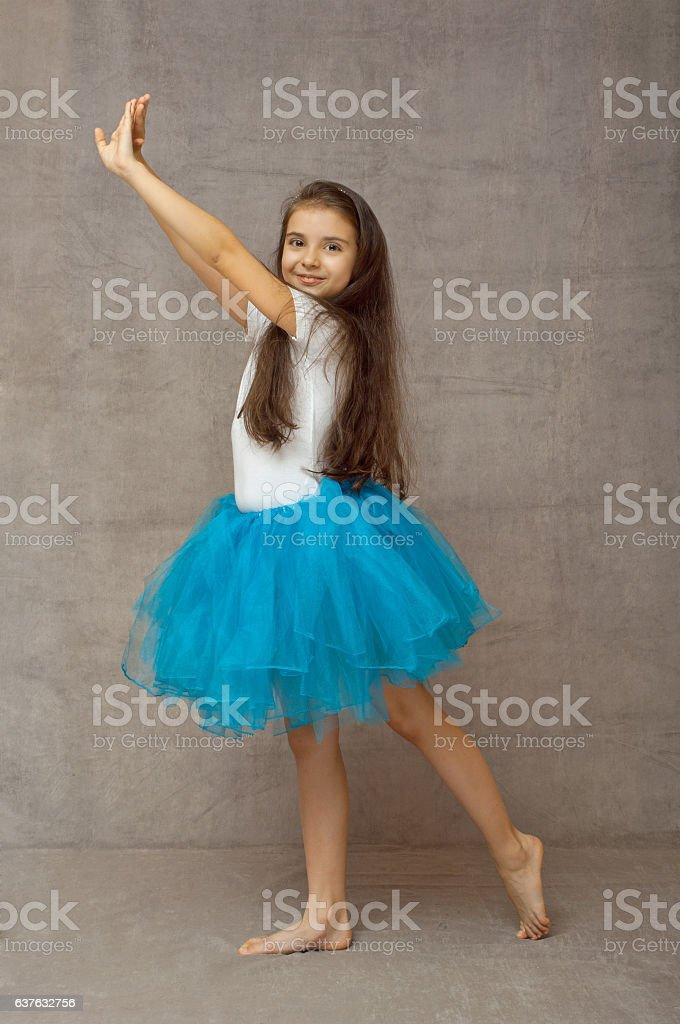 Teen ballerina in a blue tutu with long hair stock photo