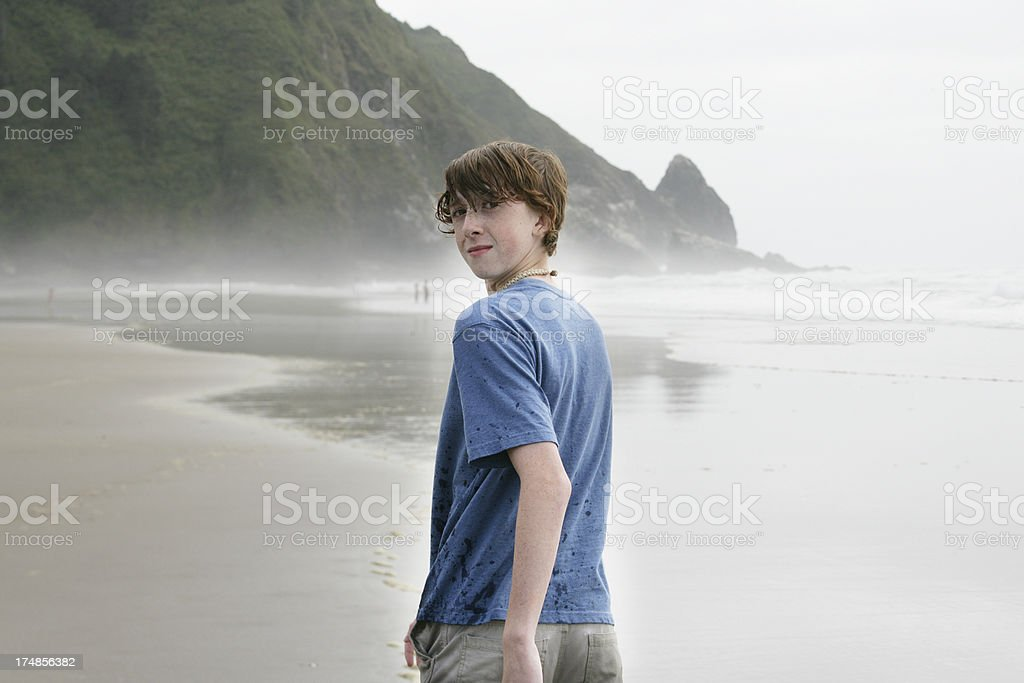 Teen Boy at Ocean Looking Over His Shoulder royalty-free stock photo