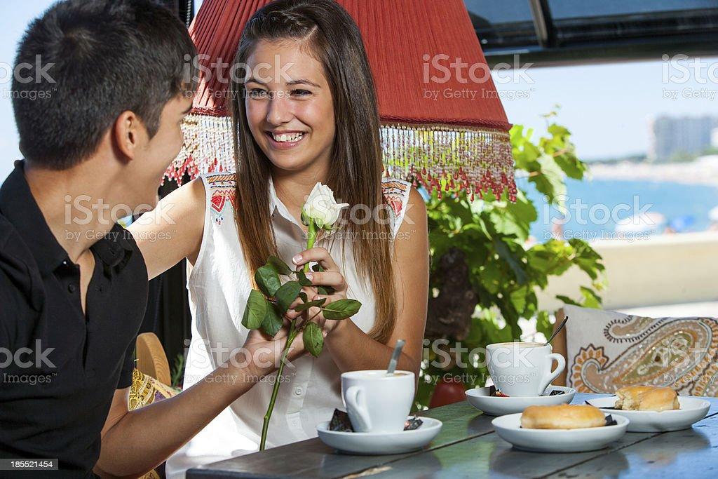 Teen garçon donne des fleurs à petite amie dans le restaurant. photo libre de droits