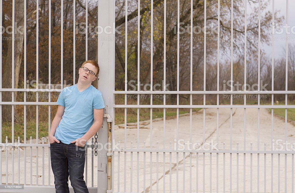 teen boy leans agains iron gate royalty-free stock photo