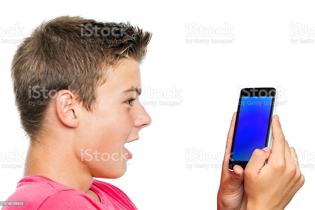 Teen garçon Regarde le téléphone intelligent surprise. photo libre de droits