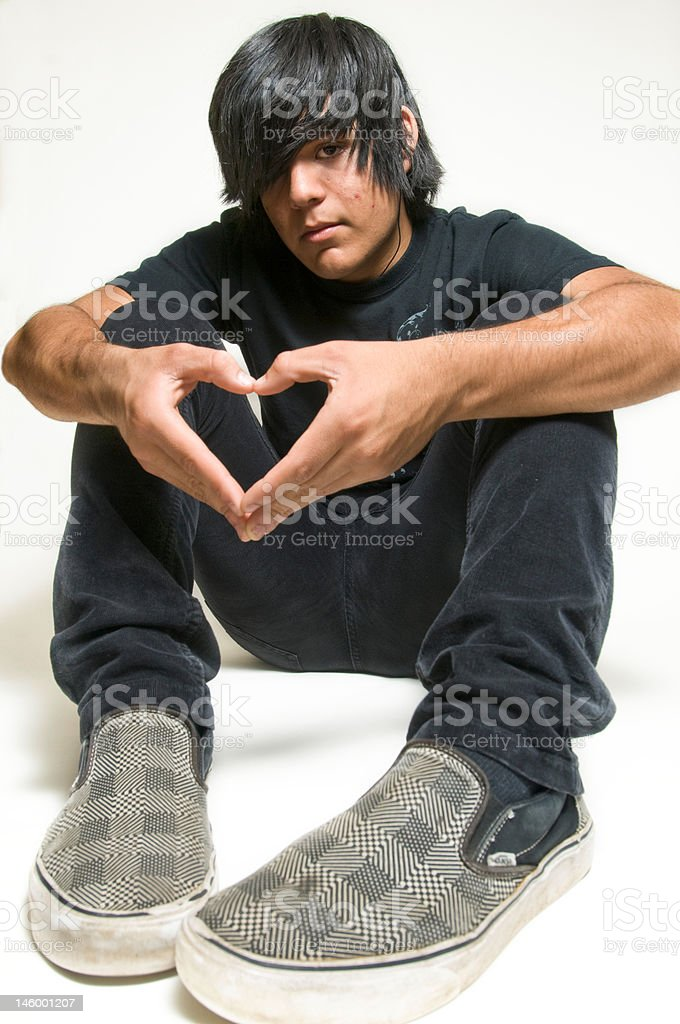 Teen boy making heart shape with hands royalty-free stock photo
