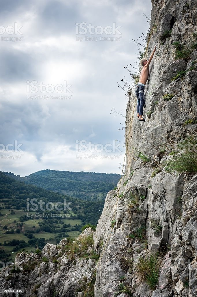 Teen boy rock climbers to the top stock photo
