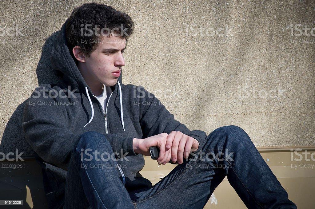 Teen Boy Sitting Against Wall royalty-free stock photo