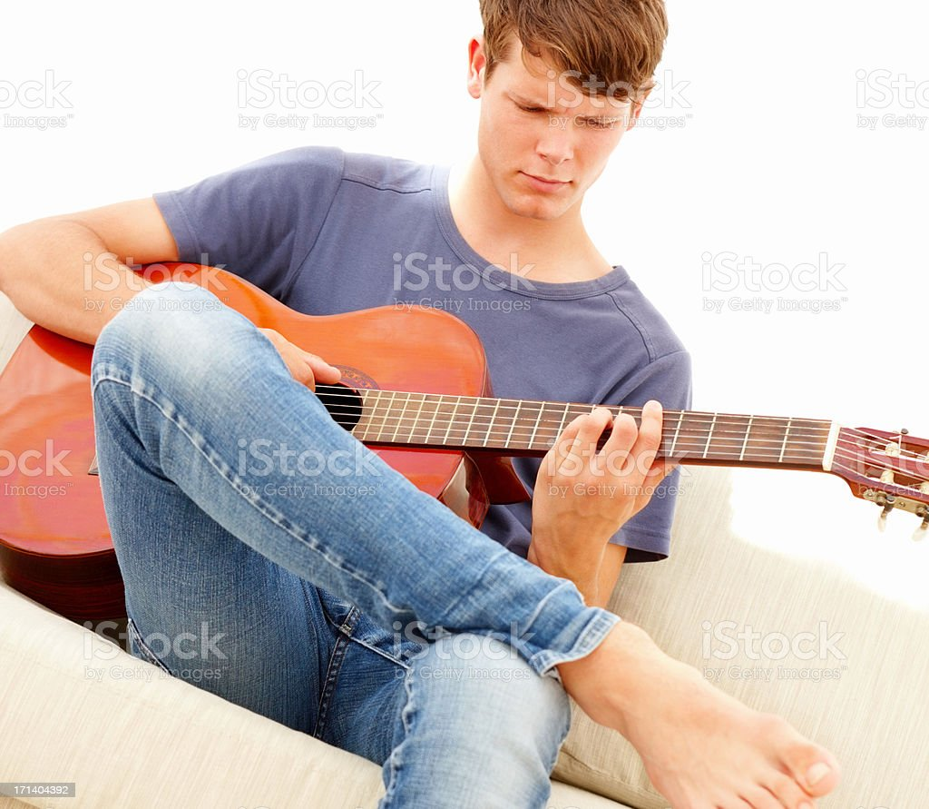 Teen boy sitting on a sofa and playing the guitar royalty-free stock photo