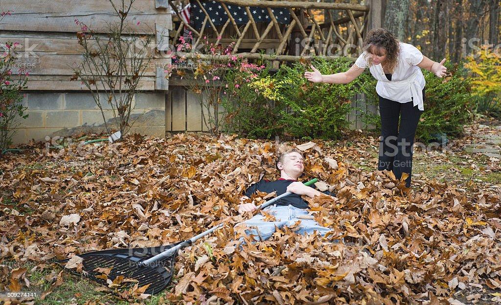 Teen boy taking a break in the autumn leaves stock photo