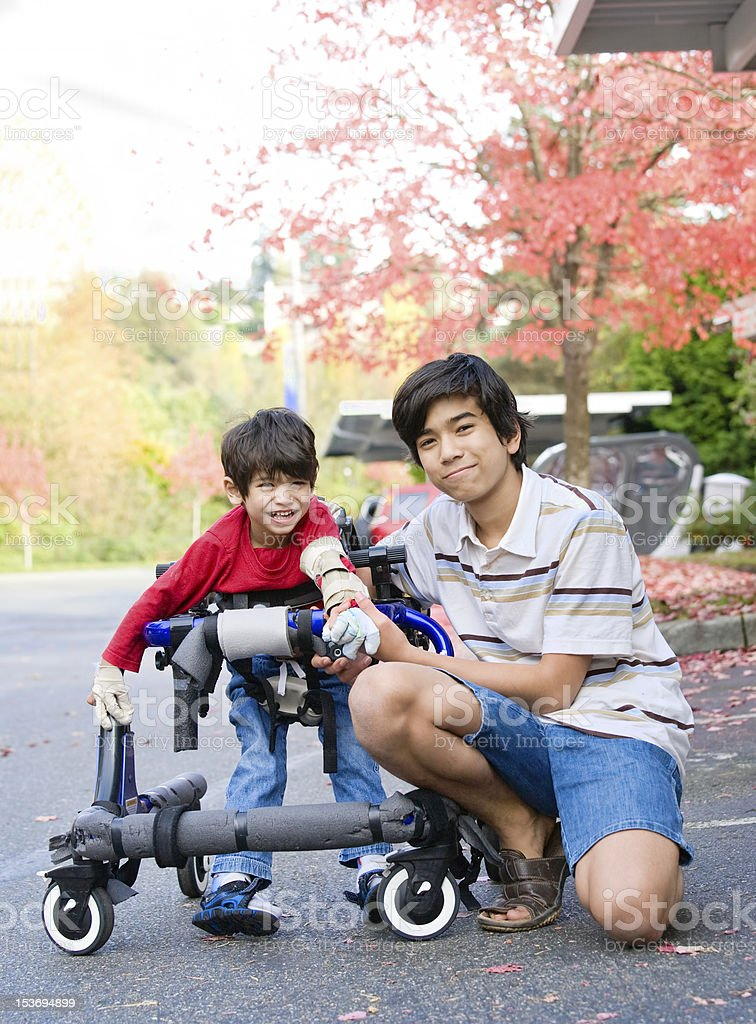 Teen boy with disabled little brother in walker royalty-free stock photo