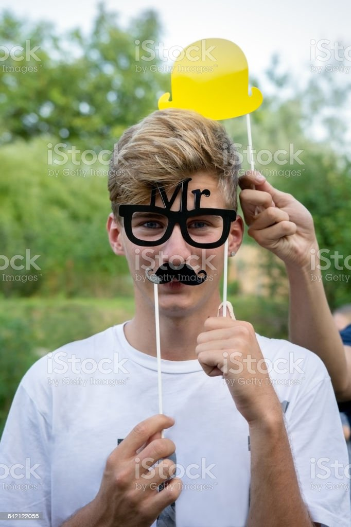 Teen boy with mustache, glasses and hat at party stock photo