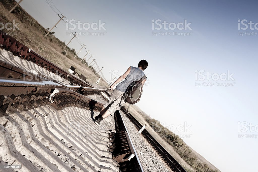 Teen boy with problems walking on rail road stock photo