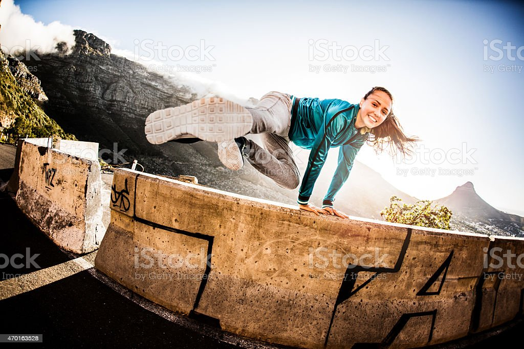 Teen breakdancing girl doing a parkour jump over a wall stock photo