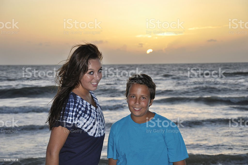 teen brother and sister by beach at sunset stock photo