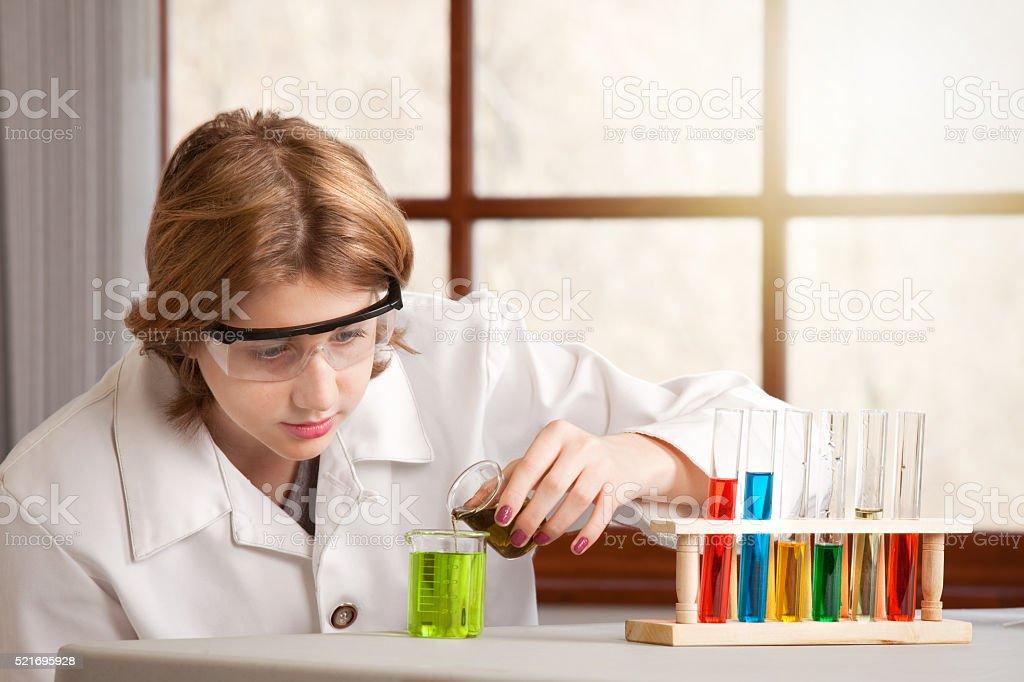 Teen Chemistry Student Pouring Liquid In Beaker stock photo