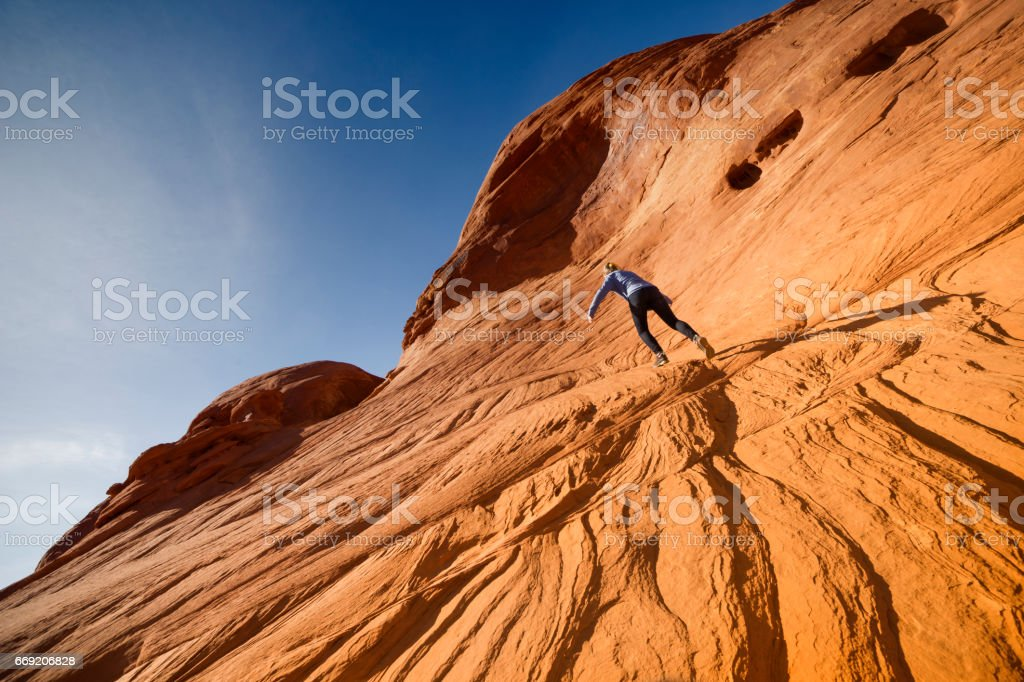 Teen climbs sandstone slopes in Monument Valley stock photo