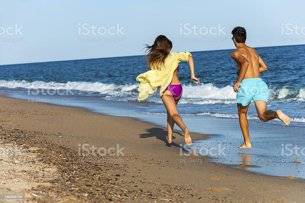 Teen couple poursuivre sur la plage. photo libre de droits