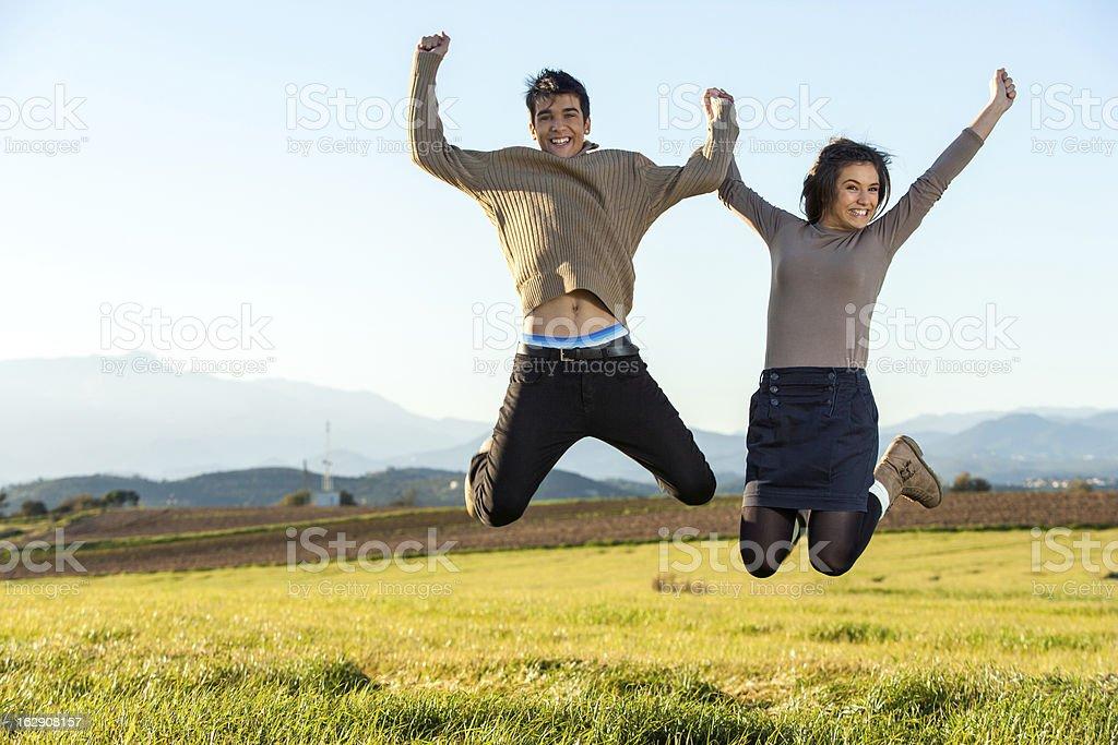 Teen couple sauter en plein air. photo libre de droits