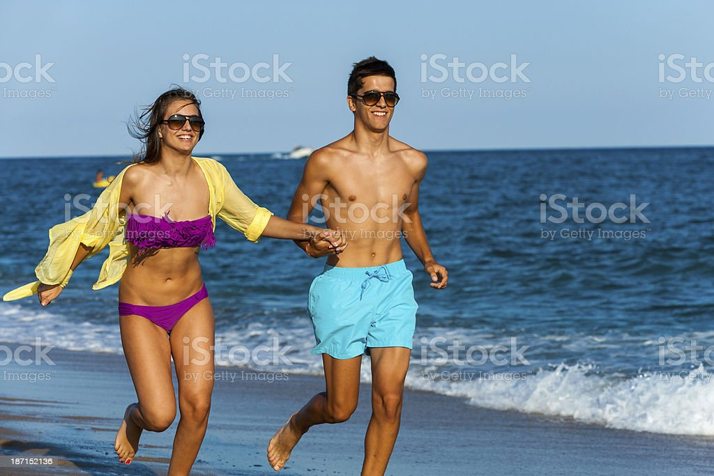 Teen couple course ensemble sur la plage. photo libre de droits